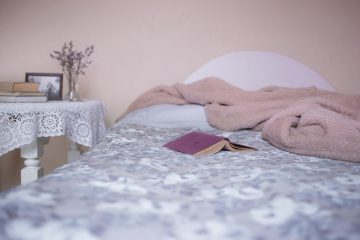 a bed with a reading book on top of the covers